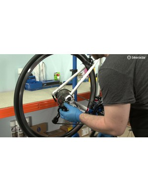 Carefully and slowly move the derailleur manually to make sure it won't allow the chain to drop off either end of the cassette