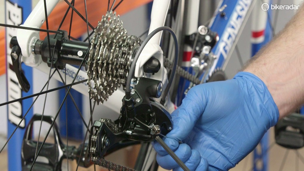 With the chain running in the second smallest cog, pull the shifter cable taut and retighten the retention bolt