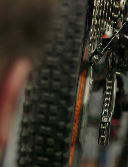 From behind the bike, sight the line of the chain as it runs over the cassette and through the upper and lower jockey-wheels