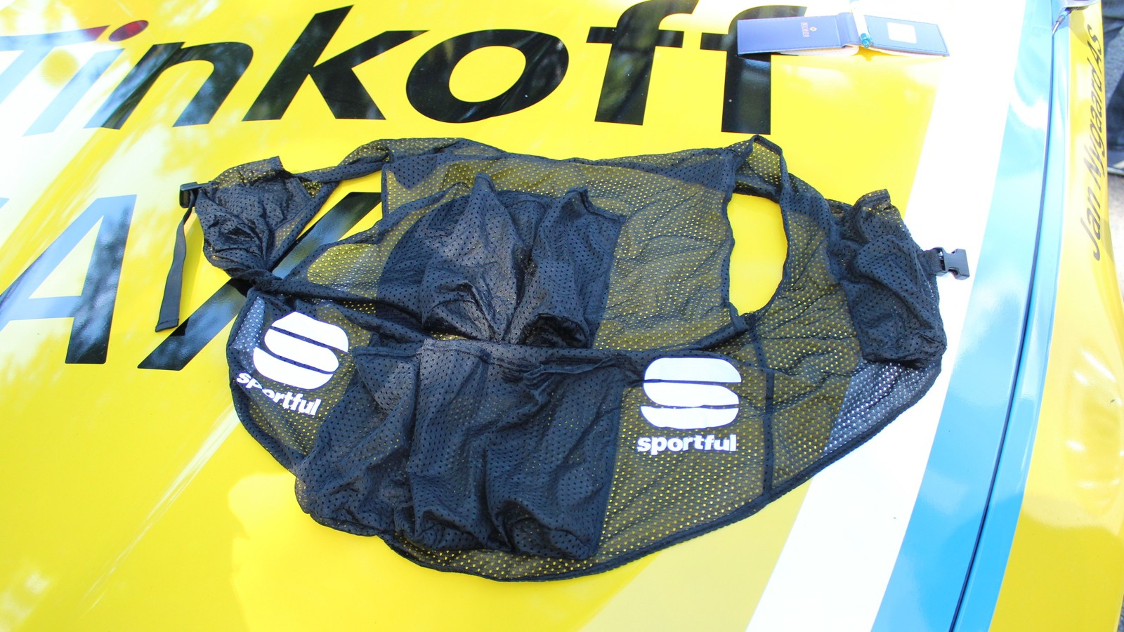 Tinkoff-Saxo Bank has a new vest for carrying seven water bottles. Instead of cramming the bottles inside a jersey, a rider just slides on this Sportful vest that a mechanic has loaded up inside the car