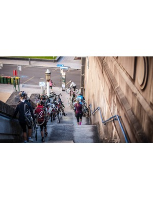 A group of riders heading down the Sydney Harbour Bridge stairs