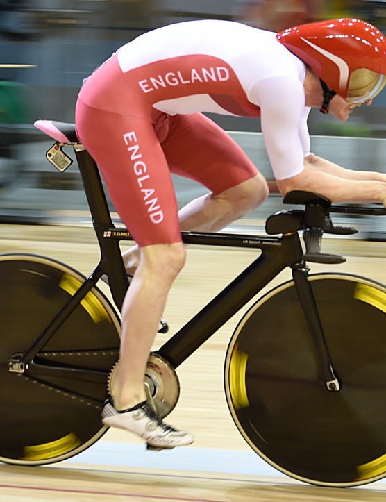 Ed Clancy aboard the UK Sport Innovation frame. The carbon base bar features torpedo bullhorns and a chunky aero stem above the straight-bladed fork. Clancy is riding a Fizik Arione Tri 2 saddle with the SRM head unit mounted beneath it