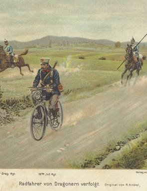 A pre-war postcard depicting a German cyclist riding along Prussian Dragoons