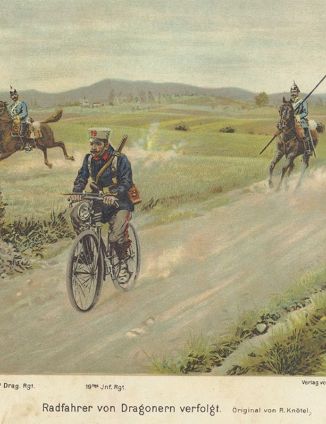 A pre-war postcard depicting a German cyclist riding along Prussian Dragoons