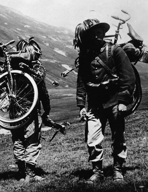 Two Italian Bersaglieri troops opt to carry the bicycles on their backs while making a mountain climb in the Alps. The Italians relied on the bicycle in their campaign against Austria
