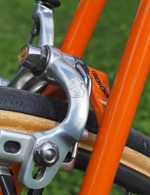 The arched shape of the brake bridge serves no real purpose aside from effectively 'hiding' behind the brake caliper