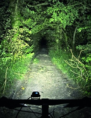 Light output is measured in lumens. This is usually a theoretical best though, and often doesn't account for lens design or beam spread, which are highly important in how much useful light is kicked onto the trail