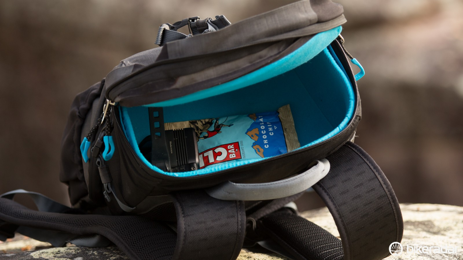 A semi-rigid top compartment offers space for a jacket, food and other small essentials