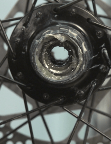 Remove the cassette, axle and bearings from the hub body, then detach the freehub itself