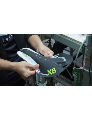 Velo uses a number of methods to manufacture saddles. In one of the more traditional ones, a finished cover is bonded to the underlying shell and foam padding by hand, with the help of a laser to ensure that it's installed straight