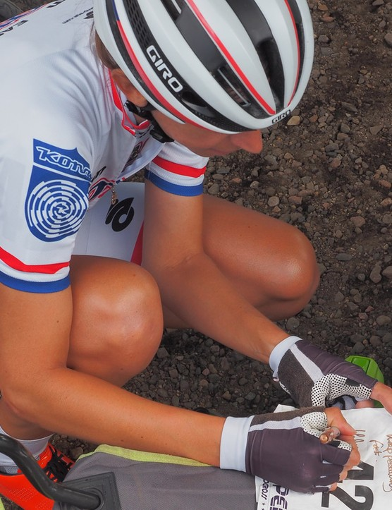 Despite being at the top of her sport, Helen Wyman is never too busy to sign some rider cards and old numbers for young fans