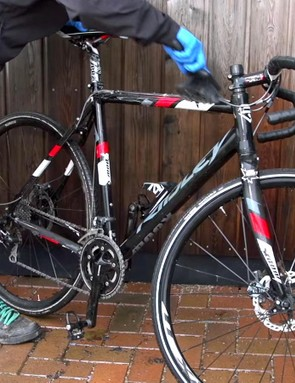 Agitate mud with a brush to loosen it from the frame and components