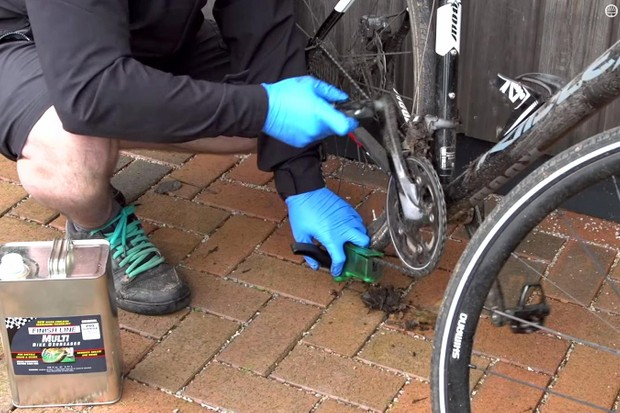 Clean the chain with a chain cleaning tool and degreaser to remove old oil