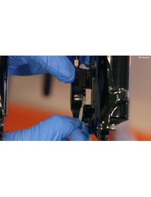 Using a brush or Q-tip, apply silicone grease to the inside of the caliper