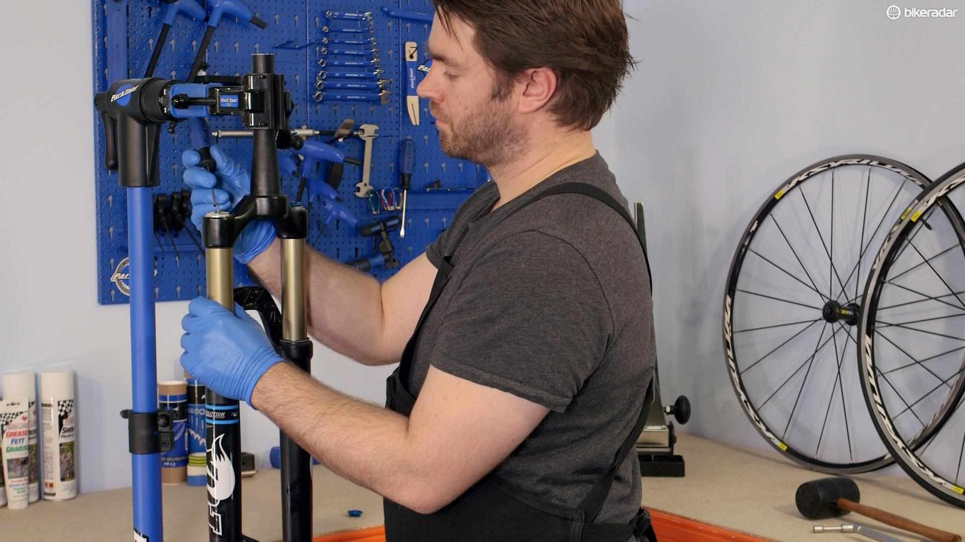 Clamp the fork in a workstand, unscrew the valve clamp and release all the air from the fork
