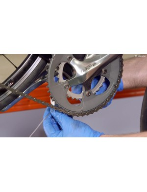 Place the thin plastic pipe on to the gear cable and feed it along until it reaches the other exit in the frame