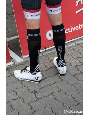 A Trek Factory Racing rider wears Bontrager podium shoes and compression socks before the race start