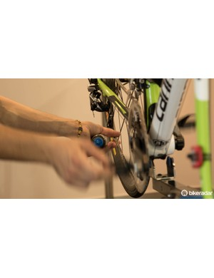 Chain lube is forced through the rollers with a bit of help. This also helps the mechanic feel for imperfections in the chain, such as a bent link