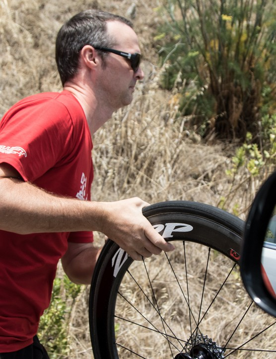 The race radio announces a Drapac rider has a flat. Crombie is out of the car as it pulls up and well on his way to fixing it