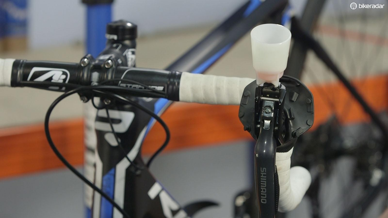 As you squeeze the syringe, fluid should begin to rise into the pot on top of the brake lever