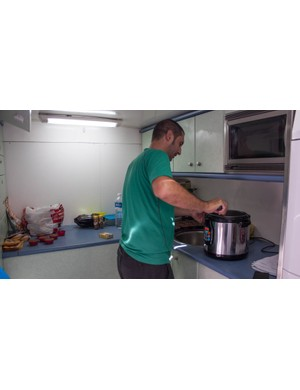 In a separate compartment, one of the team staff is making rice cakes for the riders…