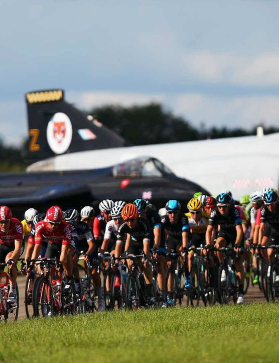 The peloton rides down the runway at Wattisham Airfield during the Tour of Britain