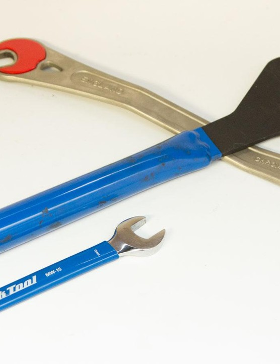 A standard 15mm spanner sits next to a workshop pedal wrench. The pros do it with leverage