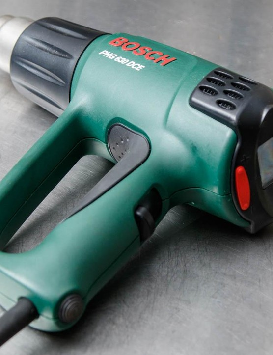 A heat gun is effectively a turbo-charged hair dryer - they're sold at most hardware stores