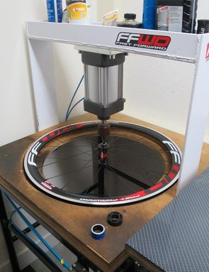 Storcel's hydraulic press stresses the spokes on both sides before his final tweaking and hand-stressing the spokes