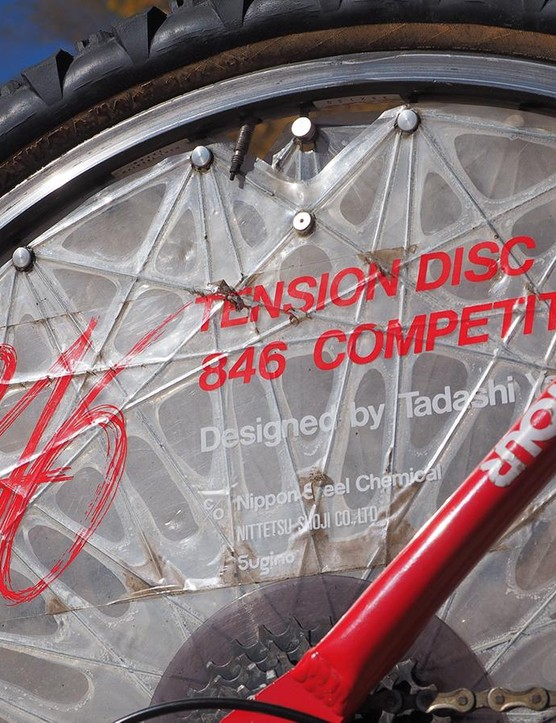 Instead of conventional stainless steel spokes, the Sugino tension disc used Kevlar strands arranged in a unique webbed layout. Performance benefits were dubious