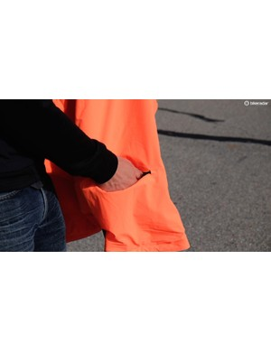 When worn orange-side-out, there's a center-back pocket. The arm holes are lined with a reflective seam, too