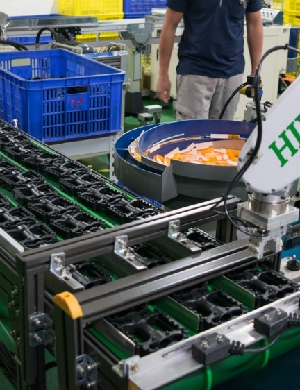 Robotic arms move pedals from one stage of manufacturing to the next