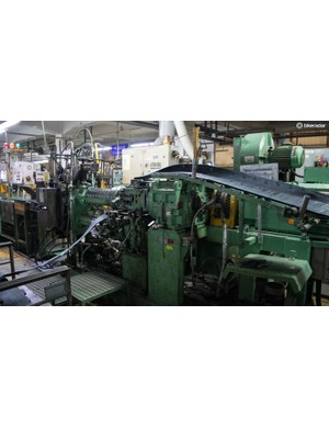 Huge machines like this one draw rubber in one end…