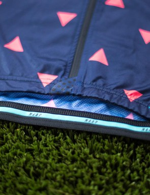 The bottom of the jersey features a silicone gripper at the back and a zipper tab to protect the bibs