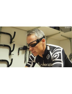 The subject is helped onto the bike, wearing these glasses that mask the lower peripheral vision