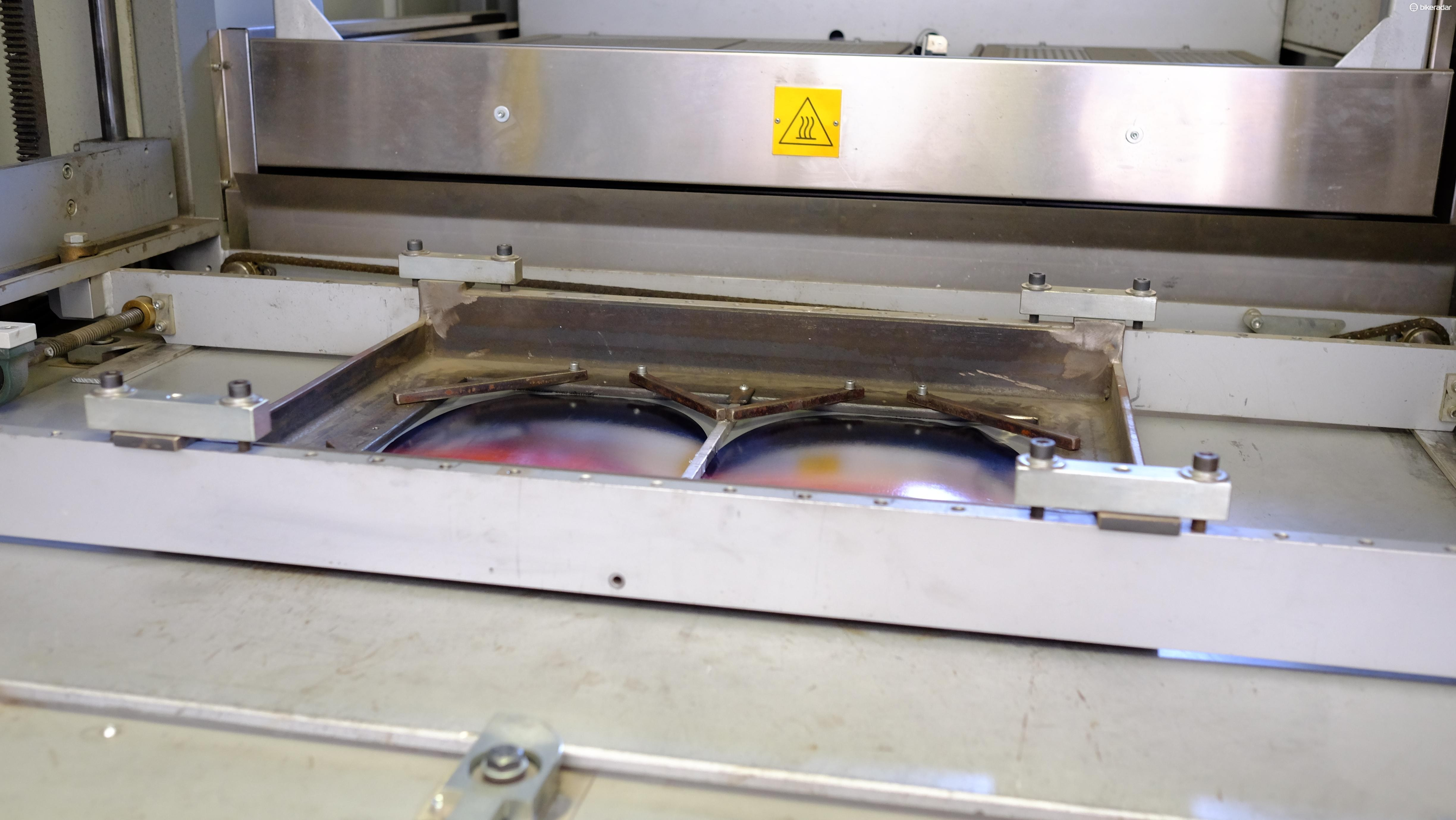 The sheets are loaded in place at the vacuum forming machine, beneath them are two helmet-shaped moulds