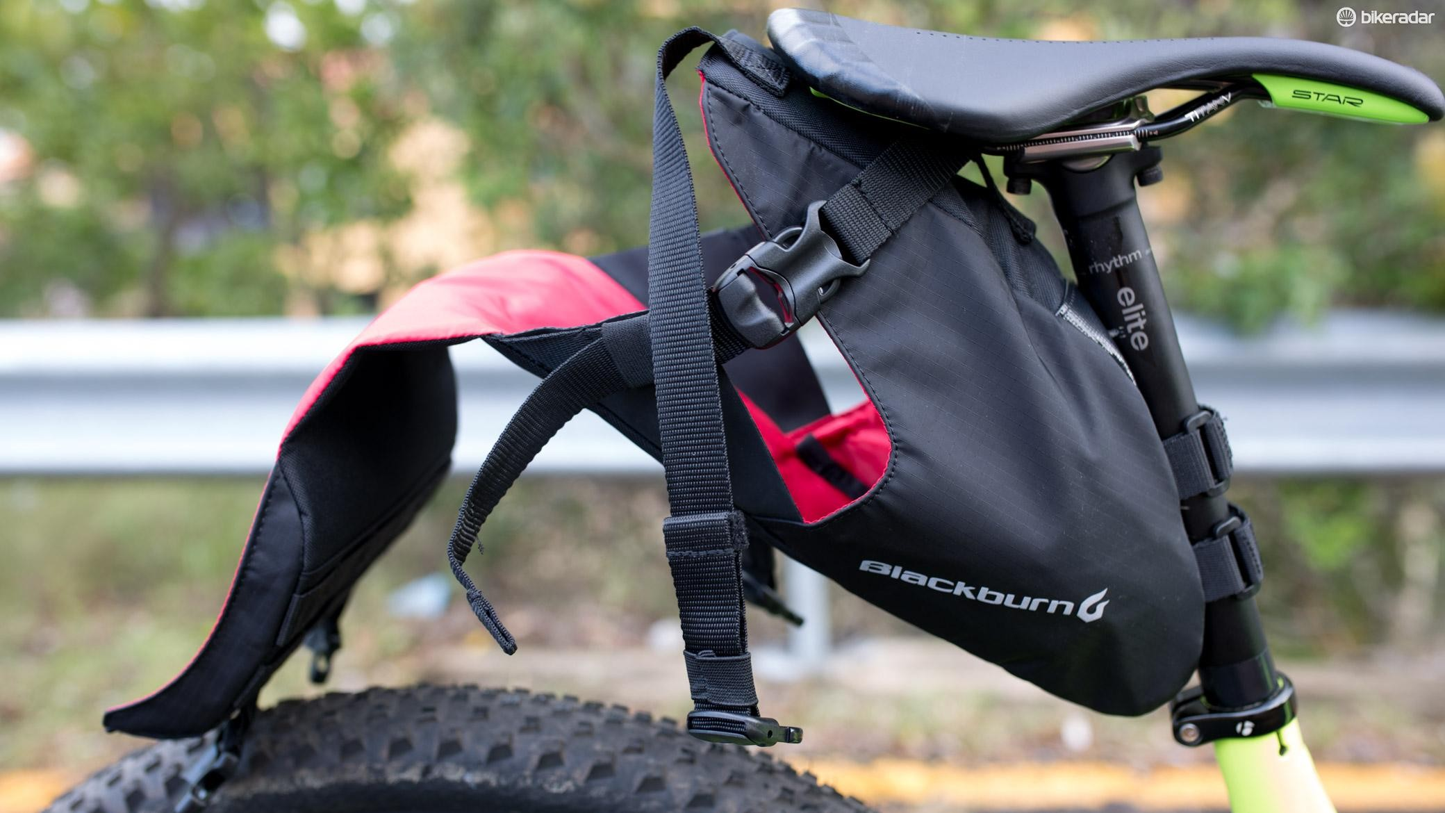 The holster allows you to adjust how far it sticks out behind the saddle based on how much you've stuffed in the dry bag