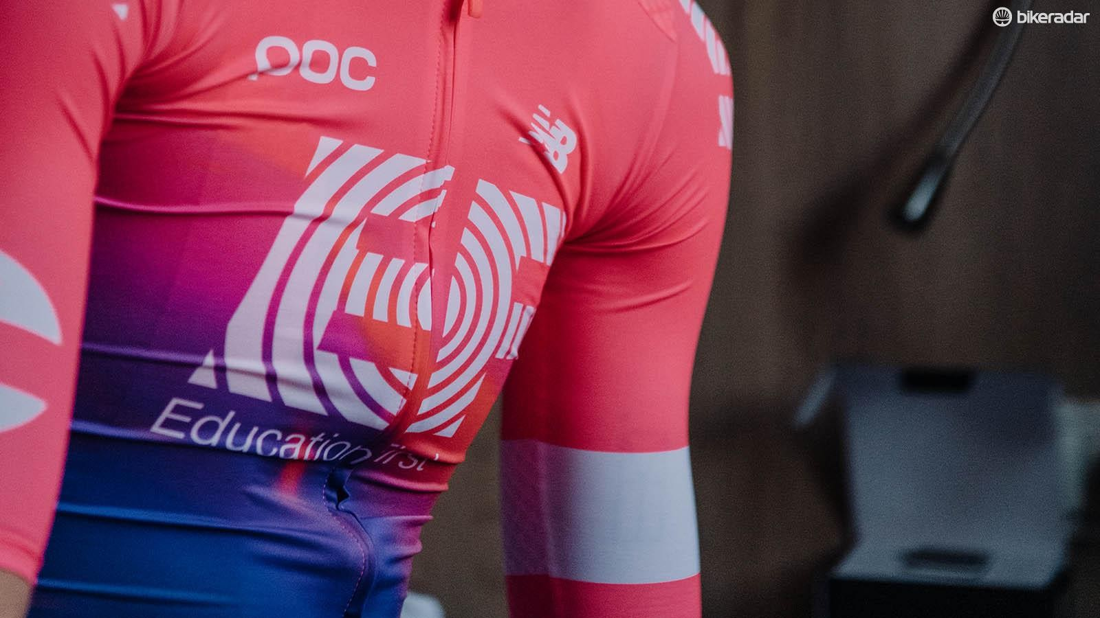 The jersey features a pink and blue fade design with contrasting white logos