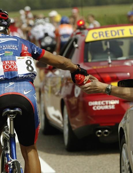 Adomestique grabs a bidon from his directeur sportif