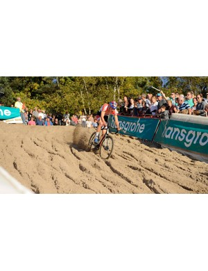 Mathieu van der Poel shows what full commitment looks like, kicking up the sand as he turns in to the descent