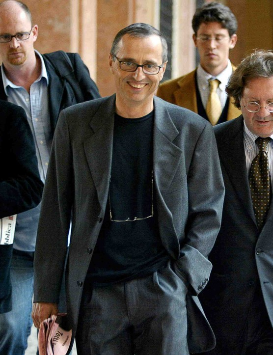 Italian sports doctor Michele Ferrari (C) leaves the Bologna's tribunal followed by journalists and his lawyer Dario Bolognesi (R), 01 October 2004. He was later acquitted of distributing doping products.