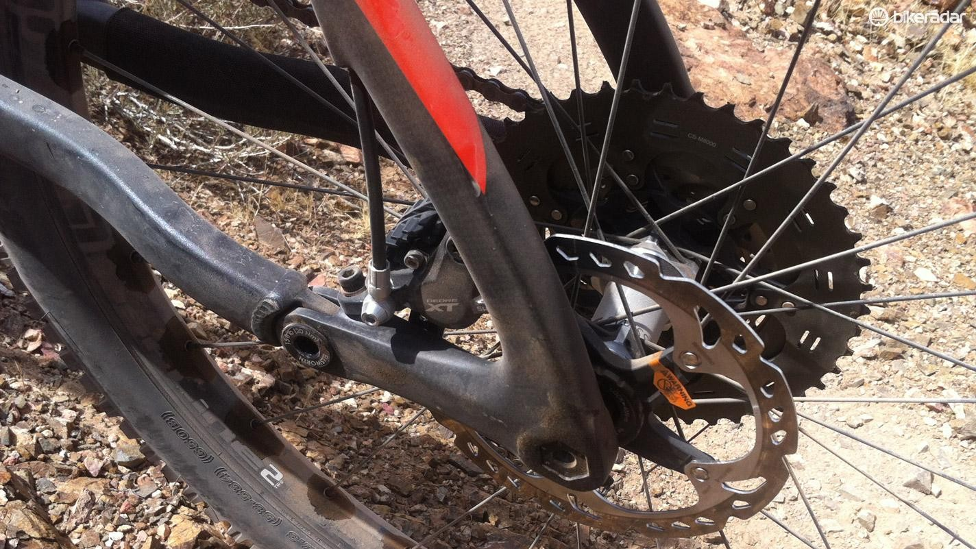 The rear disc caliper is behind the chainstay pivot and neatly tucked out of harm's way