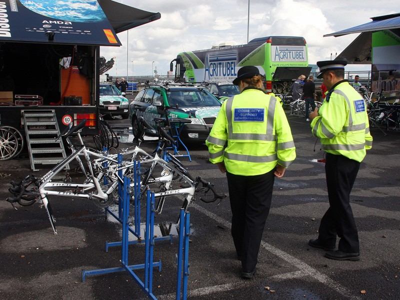 Police officers patrol in a parking lot before the Tour start in London