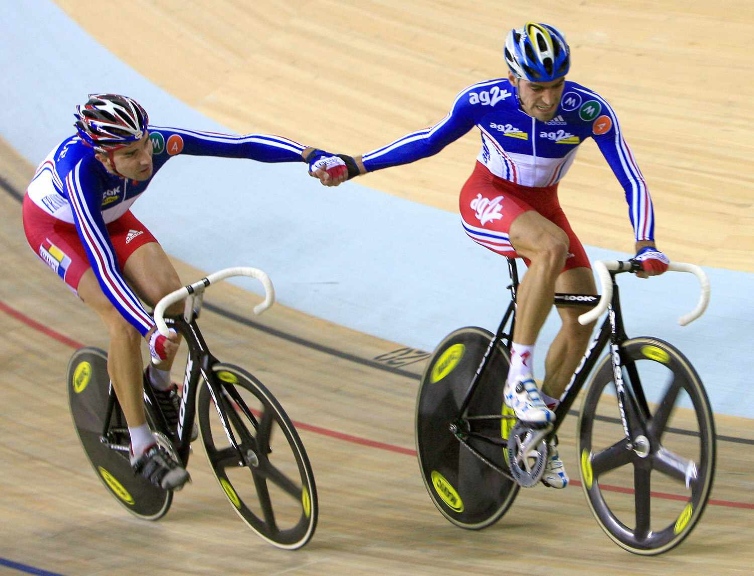 Christophe Riblon (R) of France and teammate Jerome Neuville (L) exchange during the Madison