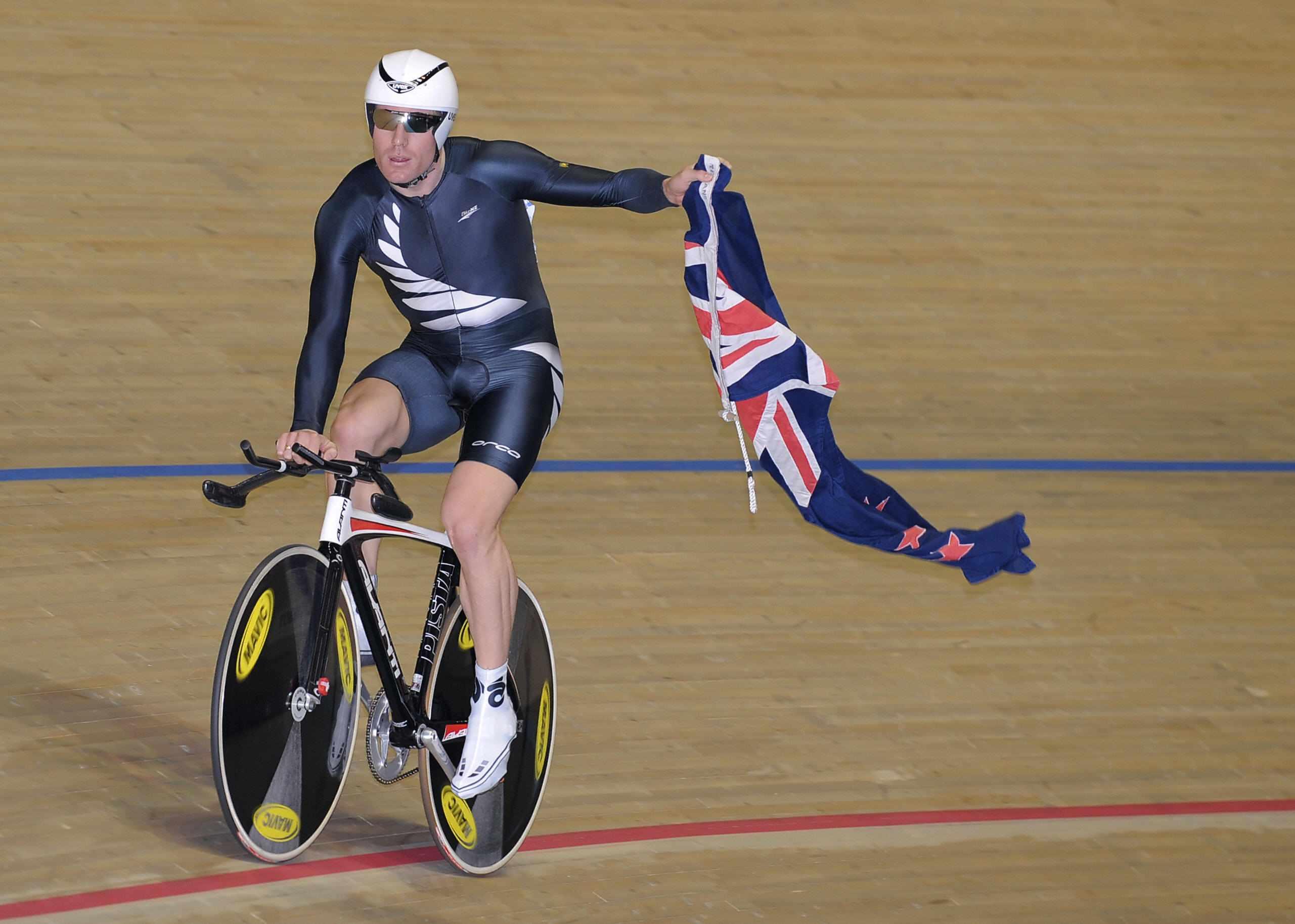 New Zealand's Hayden Godfrey flies his nation flag as he celebrates his victory in the men's omnium