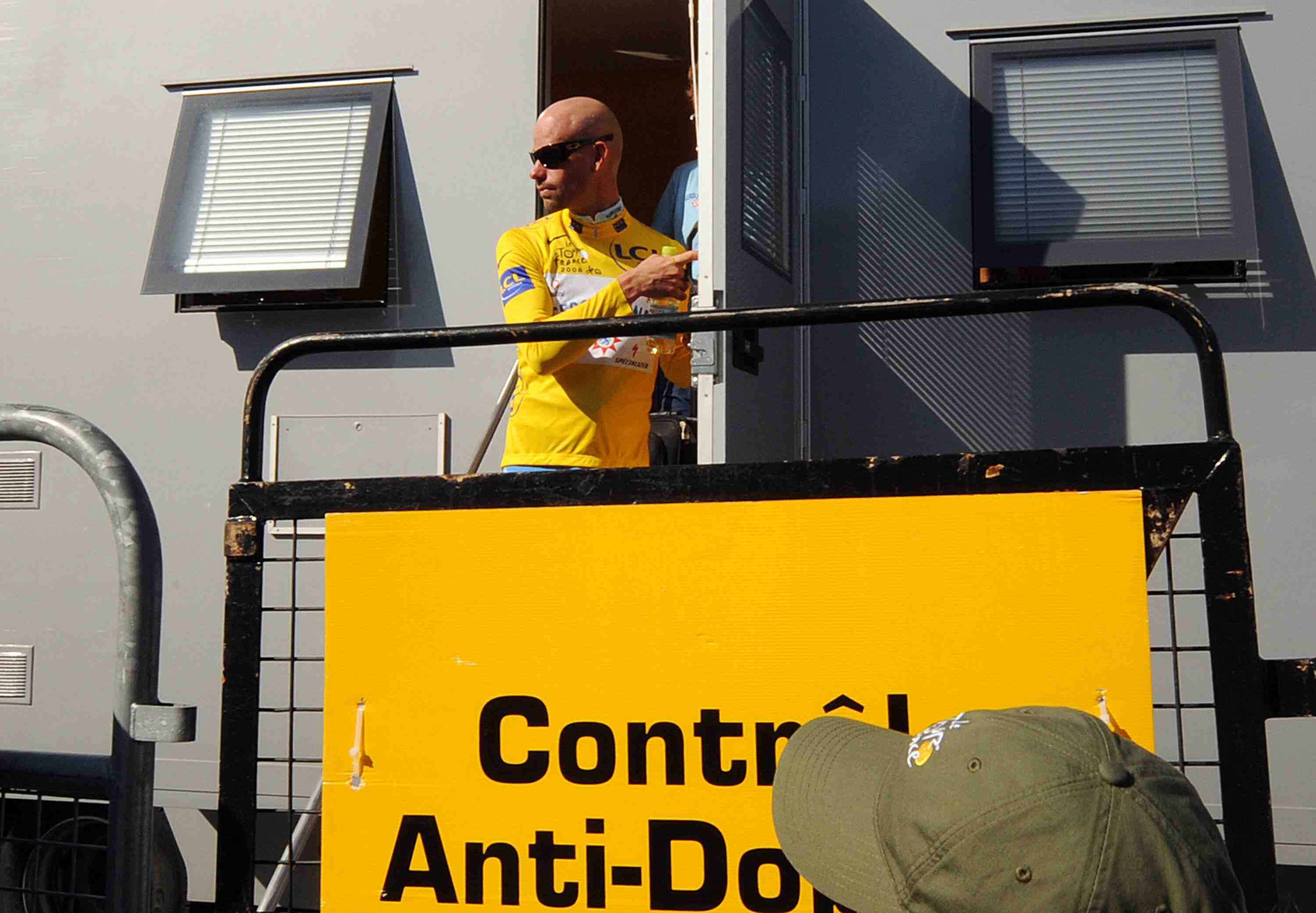 German road cyclist Stefan Schumacher leaves the doping control trailer during the early part of the 2008 Tour de France, wearing the leader's yellow jersey.