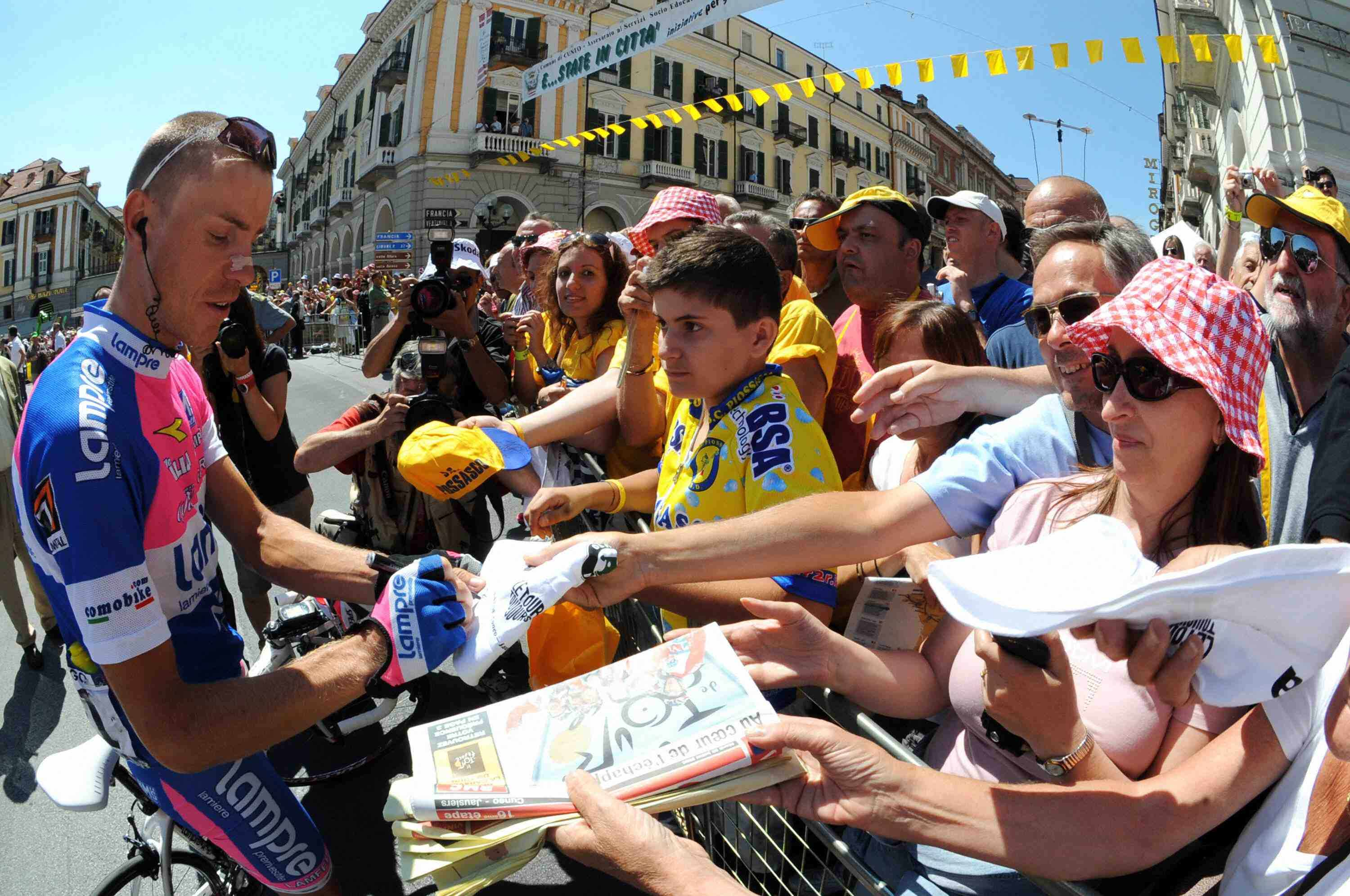 A freshly shorn Damiano Cunego signs autographs before Stage 16 in Italy.