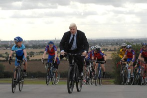Boris Johnson rides a parade lap with local youngsters.