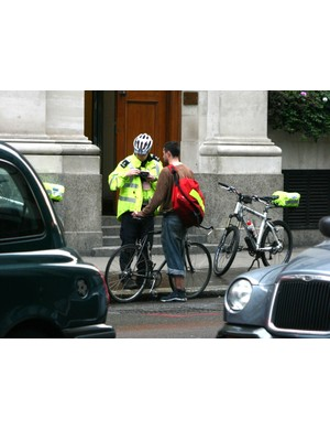 A police officer stops a cyclist