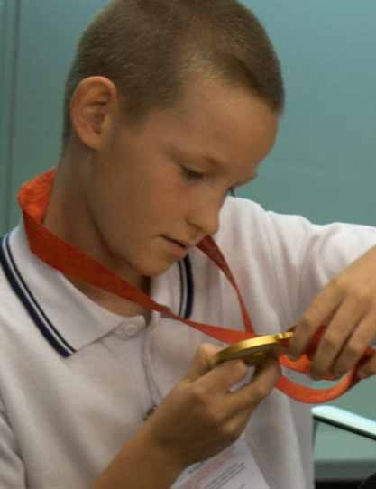 A pupil checks out Paul's gold medal.